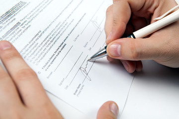 the man's hand signs the document and the signature