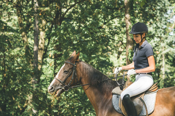 Young woman riding horse in nature