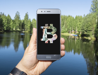 Bitcoin (Crypto currency) on a mobile device, with a lake view in the background. Crypto currency can be used anywhere, in this case its used on a lakefront in Finland.