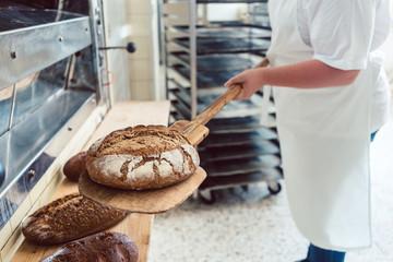 Bäcker Frau in Backstube legt Brot auf Brett ab