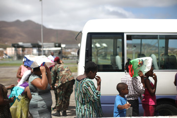 Women protect themselves from the sun with bags as they form a line to get baby food following Hurricane Irma on Sint Maarten