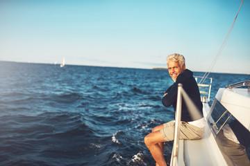 Mature man enjoying the ocean view from his sailboat Wall mural