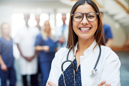 Smiling young doctor standing in front of medic team