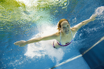 Underwater View Of A Young Woman Jumping Into The Water