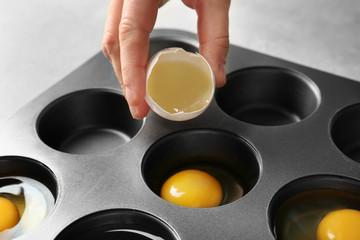 Woman cracking egg into muffin tin, closeup