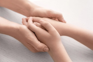 Mother and daughter holding hands together on light background, closeup