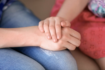 Mother and daughter holding hands together, closeup