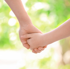 Mother and daughter holding hands together on blurred background