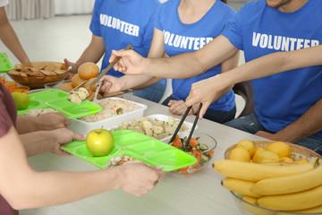 Volunteers serving food for homeless people indoors
