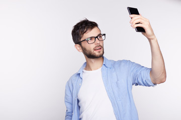 Handsome young male with black hair, stylish glasses & beard holding mobile phone, posing for selfie, looking at camera with flirty smile. Attractive metrosexual guy admiring himself at phone camera.