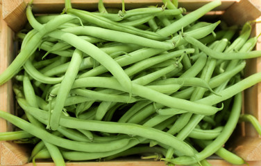 Raw fresh organic green beans in wooden crate, close up