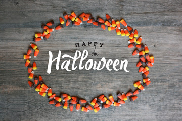 Wall Mural - Happy Halloween Calligraphy With Candy Corn Oval Border Over Rustic Wooden Background, Horizontal
