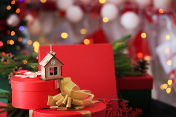 Decorative house on Christmas gift box against blurred background