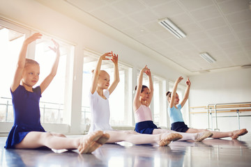 Cute little ballerinas sitting on floor with hands up