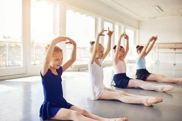 Little ballet dancing girls on floor with hands up