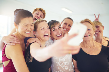 Group of laughing friends taking selfies in a dance studio