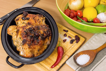 Roasted turkey thigh with cranberry in roasting pan on a wooden board.