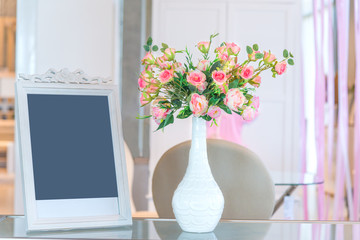 Rose in white vase and white picture frame interior