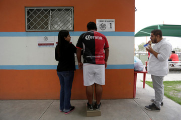"A man uses a weighing scale before his ""Futbol de Peso"" (Soccer of Weight ) league soccer match, a league for obese men who want to improve their health through soccer and nutritional counseling, in San Nicolas de los Garza"