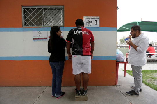 """A man uses a weighing scale before his """"Futbol de Peso"""" (Soccer of Weight ) league soccer match, a league for obese men who want to improve their health through soccer and nutritional counseling, in San Nicolas de los Garza"""