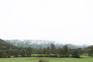 View of cloud draped mountain with fog and green fields below