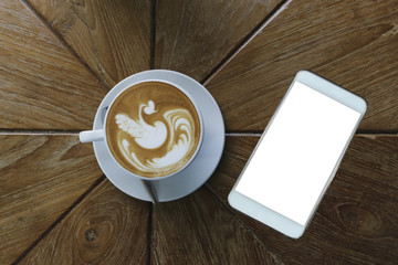 Top view of coffee latte art style in white ceramic cup besides white smart phone with blank white screen on wooden table background,mock up image