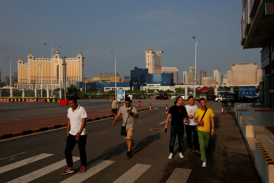 People walk near the border checkpoint of Hengqin Island with Macau's casinos seen at background