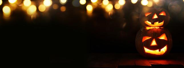 Halloween Pumpkin on wooden table in front of spooky dark background. Jack o lantern Fotoväggar