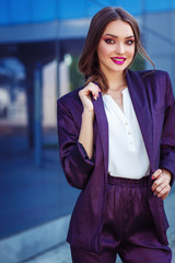 Young woman posing in purple suit. Fashion makeup