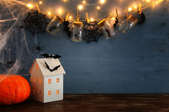 Halloween holiday concept. Mysterious house with lights in front of masson jars with spiders, baths