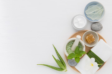 Homemade skin care and body scrub with natural ingredients honey, salt, mint, natural lotion and aloe vera set up on white wooden background.