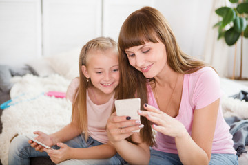 Beautiful mother and her little daughter are using a smartphone and smiling at home. Happy loving family.