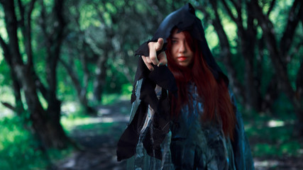 Dark forest with young witch