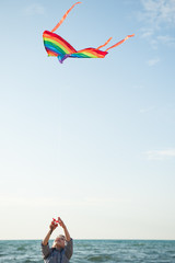 happy little boy holding a kite on sky and sea background