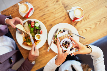 Couple of young people taking photo of their food while eating breakfast in a cafe before going to work