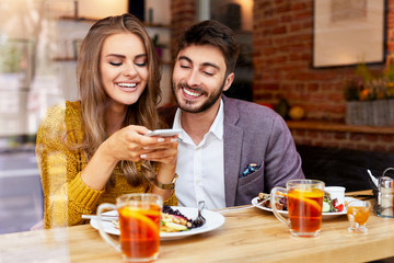 Cheerful young couple sitting together and eating breakfast in cafe taking photo of their food and smiling