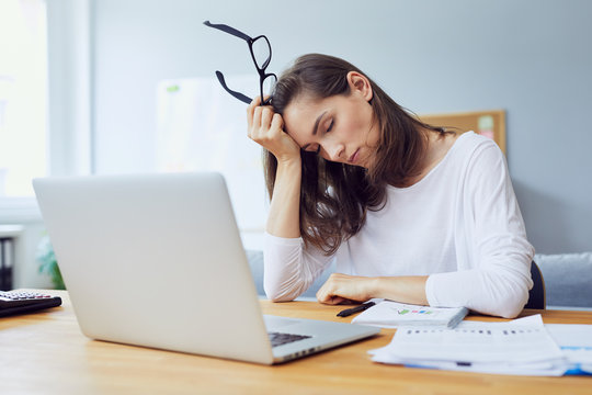 tired young office worker at desk while trying to work in modern office