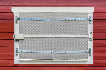 Closed window on red exterior wood wall with security fittings, bars, lock and metal shutters.