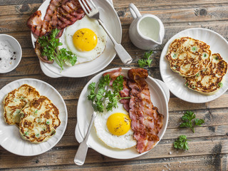 Full breakfast table - fried eggs with bacon and potatoes, green peas, leek pancakes on a wooden table, top view