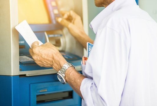 Men are pressing money from the ATM.