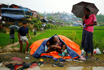 Rohingya refugees sit on the roadside as they take shelter during rain in Cox's Bazar