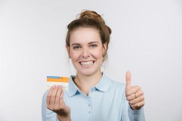 Junge Frau zeigt Daumen hoch und ihren Organspendeausweis