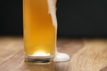 wheat unfiltered beer poured into glass on wood board