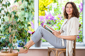 pretty middle-aged woman with a book near an open window