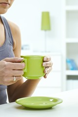 Close up of woman having a cup of tea at home