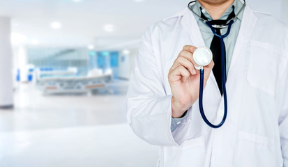 Doctor holding a stethoscope on background of Hospital ward
