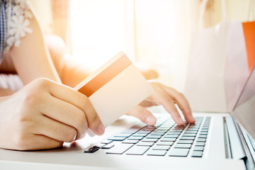 Closeup credit card ,Woman shopping online using laptop with credit card enjoying in home