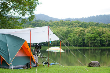 nature orange with green camping tent and gray fly sheet with tent accessory on meadow with lake or river and tree mountain for holiday relax on rainy season and white sky at ched khot
