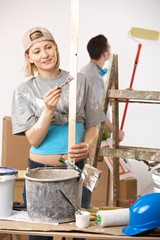 Happy couple busy renovating painting new home