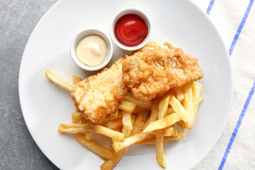 Plate with tasty fried fish, chips and sauces on table